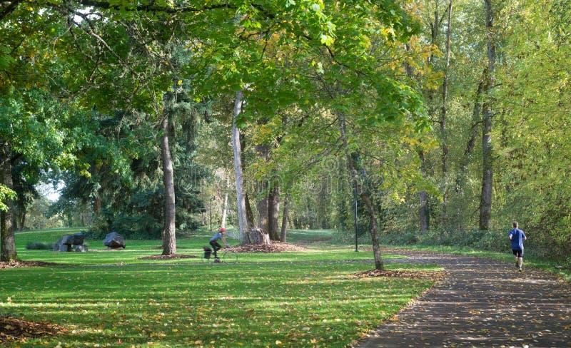 Велосипед и бегун в парке стоковая фотография rf
