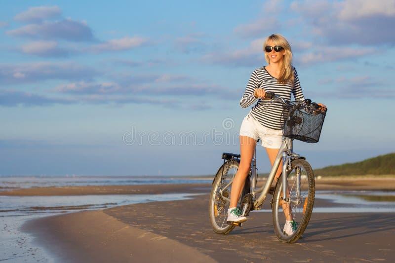 Велосипед катания модной женщины на пляже на заходе солнца стоковые фото