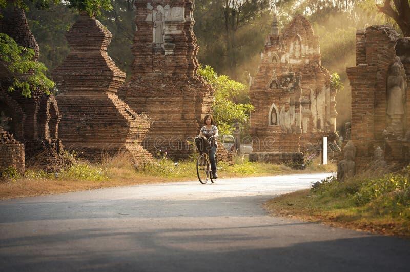 Велосипед катания молодой дамы в древнем городе стоковое фото rf