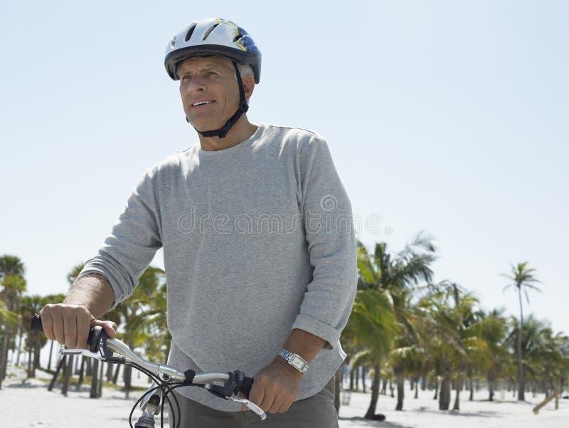 Велосипед катания старшего человека на тропическом пляже стоковое фото rf