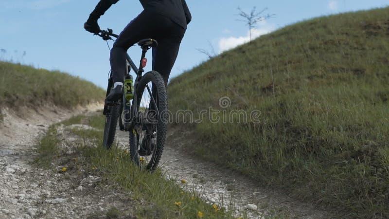 Велосипед катания человека вверх по холму травы горы видеоматериал