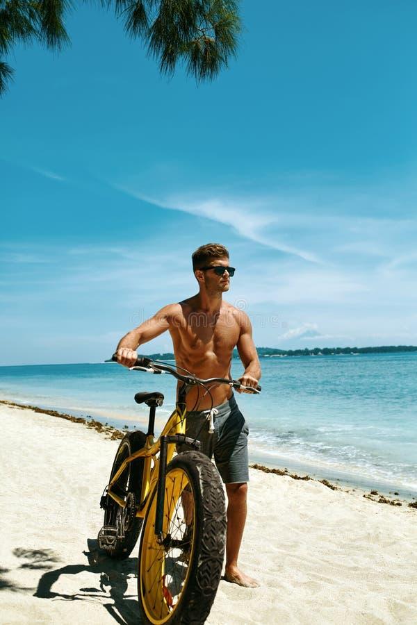 Велосипед песка катания человека на пляже Деятельность при спорта лета стоковое фото