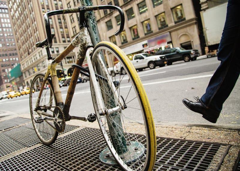 Велосипед прицепленный на знаке улицы стоковые изображения
