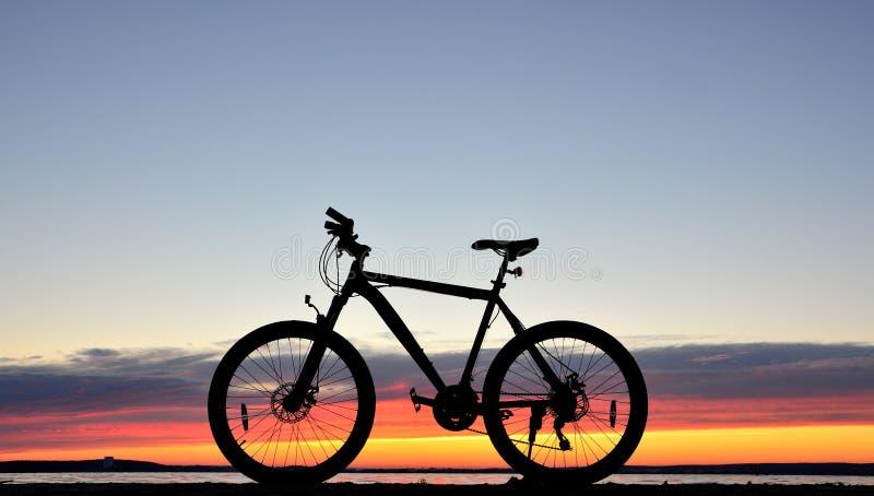 Велосипед против захода солнца стоковые фото