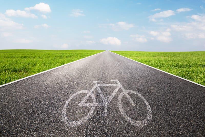 Велосипед символ на длинной прямой дороге асфальта, путь стоковое фото rf