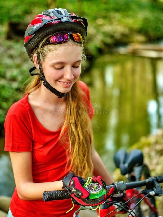 Велосипеды задействуя шлем девушки нося смотрят компас стоковое фото