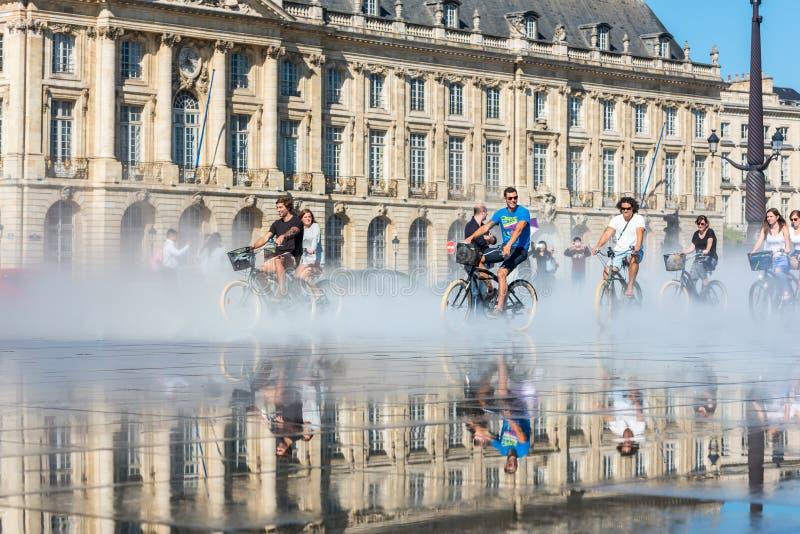 Велосипеды людей ехать в фонтане в Бордо, Франции стоковое изображение