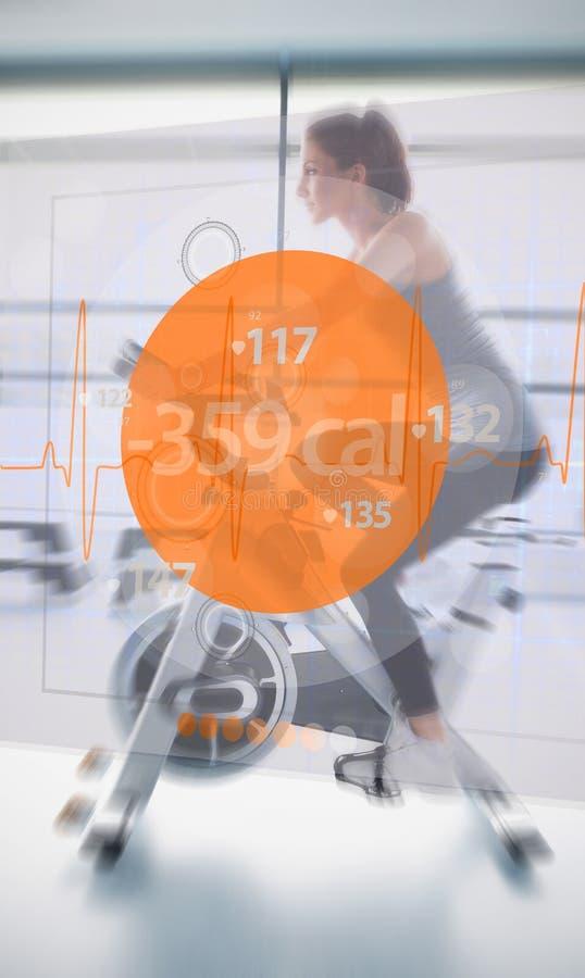 Велотренажер катания женщины с футуристическим интерфейсом рядом с ей стоковые изображения rf
