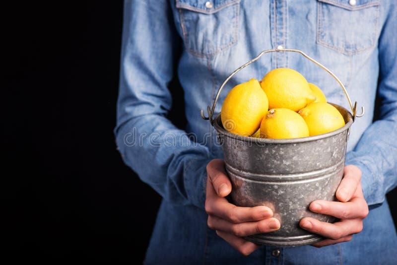 Ведро лимонов в руках стоковое изображение