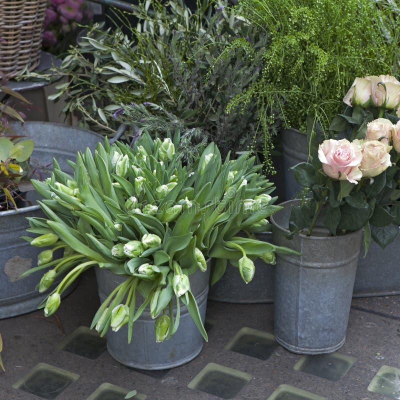 Ведро с букетом белых тюльпанов и вазы с красными розами как украшение для входа дома стоковое изображение rf