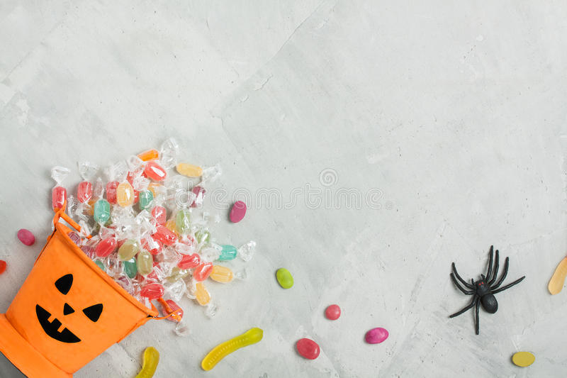 Ведро хеллоуина оранжевое с конфетами, jujubes, и резиновым пауком стоковое изображение