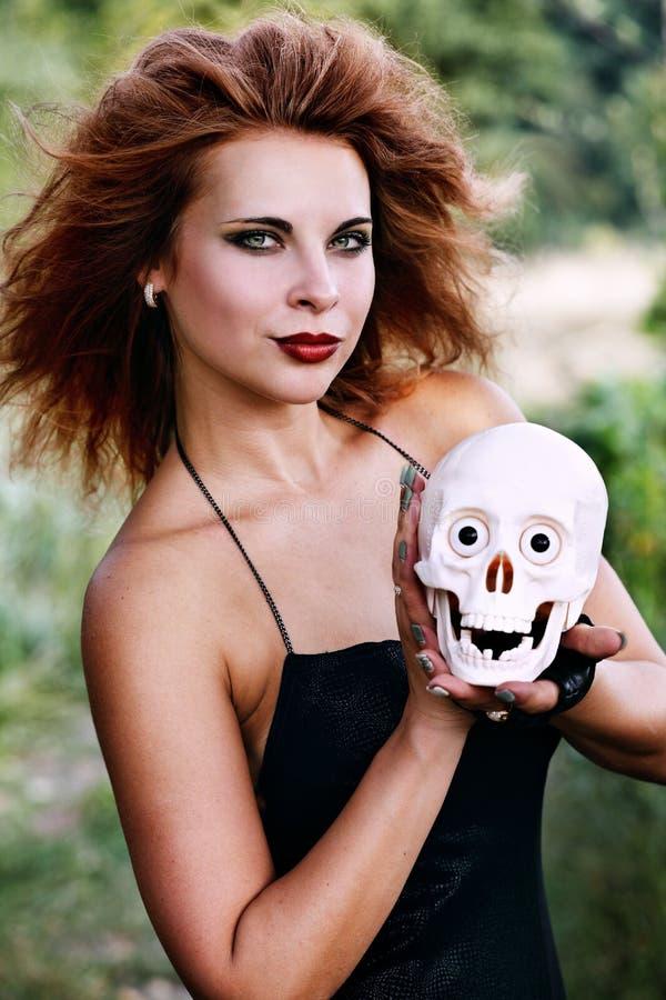 Ведьма держа человеческий череп стоковые изображения rf