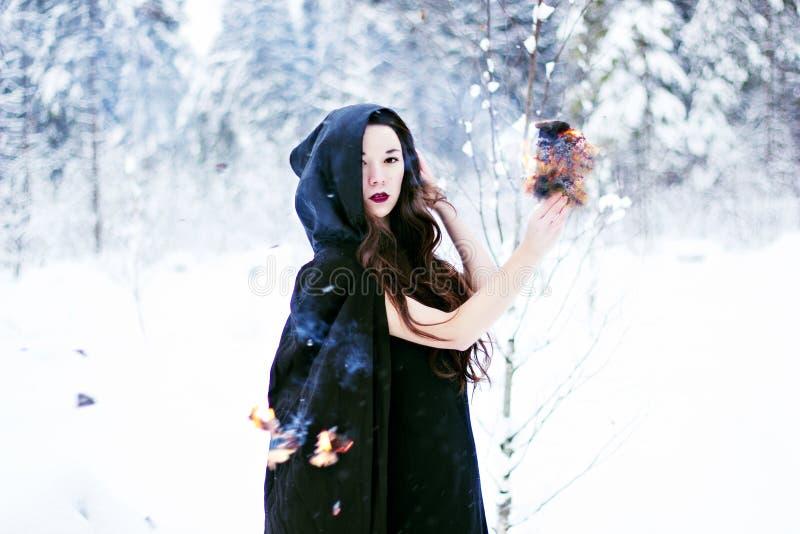 Ведьма или женщина в черном плаще с шариком огня в белом лесе снега стоковая фотография rf