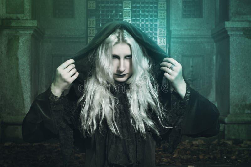 Ведьма одетая чернотой и волшебные света стоковые изображения