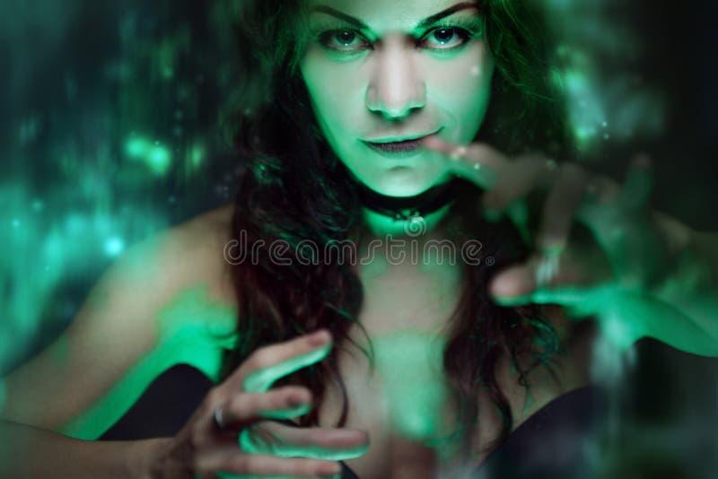 Ведьма создает волшебство Красивая и сексуальная женщина с мистическим светом стоковое фото