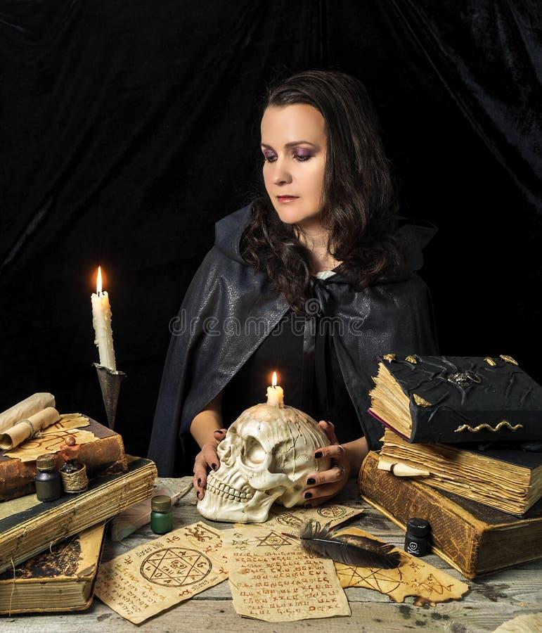 Ведьма с черепом и книгами стоковое фото