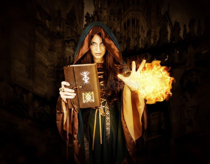 Ведьма хеллоуина держа волшебную книгу при runes делая волшебство стоковые изображения rf