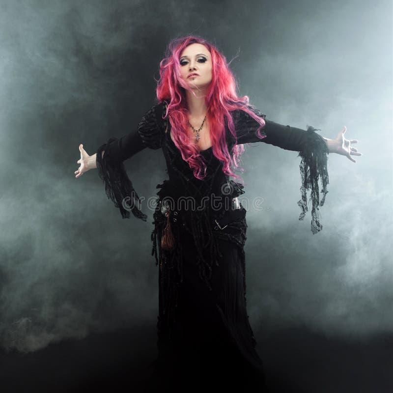 Ведьма хеллоуина создает волшебство Привлекательная женщина с красными волосами в ведьмах костюмирует оружия протягиванные положе стоковое изображение