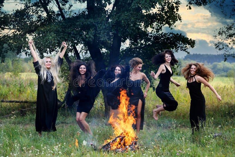 Ведьмы смеясь над вокруг лагерного костера стоковое фото