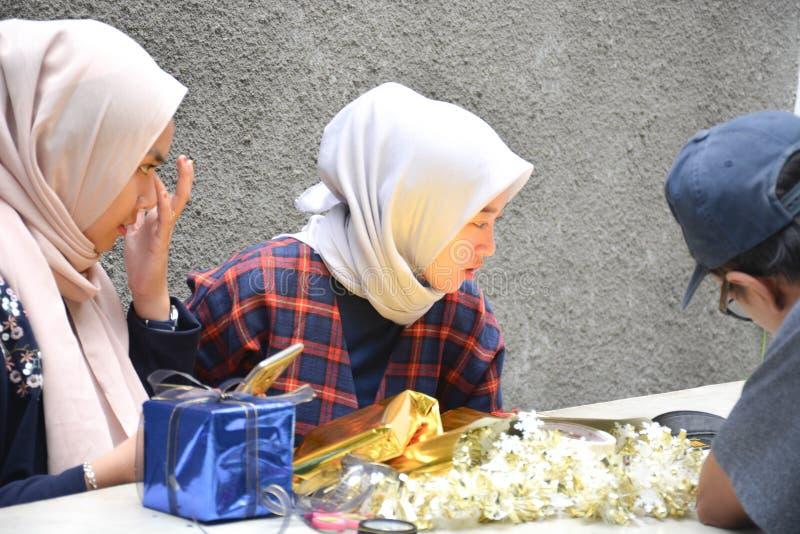 Взаимодействие между мужским фотографом с hijab 2 женским на таблице стоковые изображения rf
