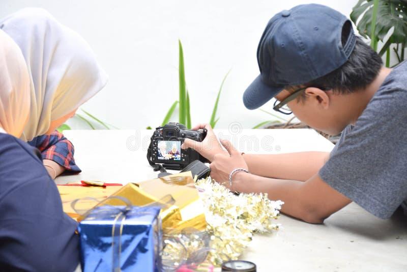 Взаимодействие между мужским фотографом с hijab 2 женским на таблице стоковые изображения