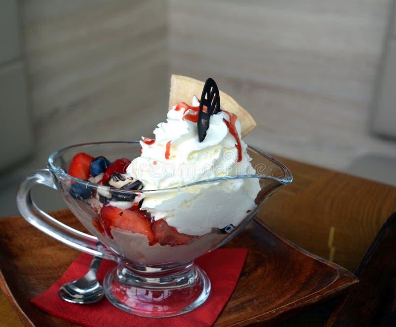Взбитые сливк и мороженое с горячими плодоовощами на стеклянном шаре стоковая фотография