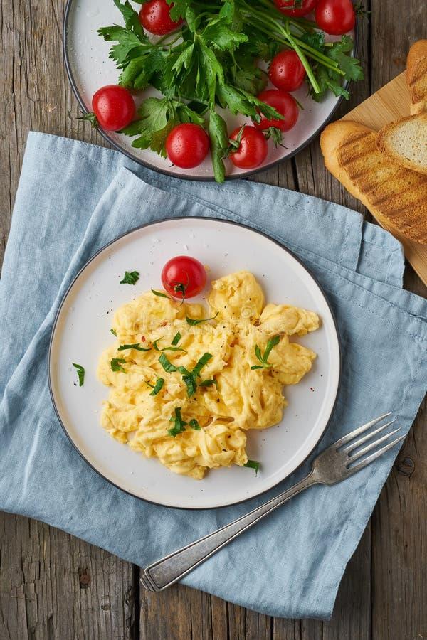 Взбитые яйца, омлет, взгляд сверху, вертикаль Завтрак со все-зажаренными яйцами, чашка чаю, томаты на старом деревянном столе стоковое фото rf