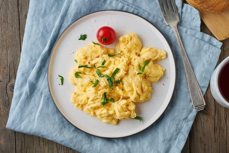 Взбитые яйца, омлет, взгляд сверху, конец вверх Завтрак со все-зажаренными яйцами, чашка чаю, томаты на старом деревянном столе стоковое фото rf