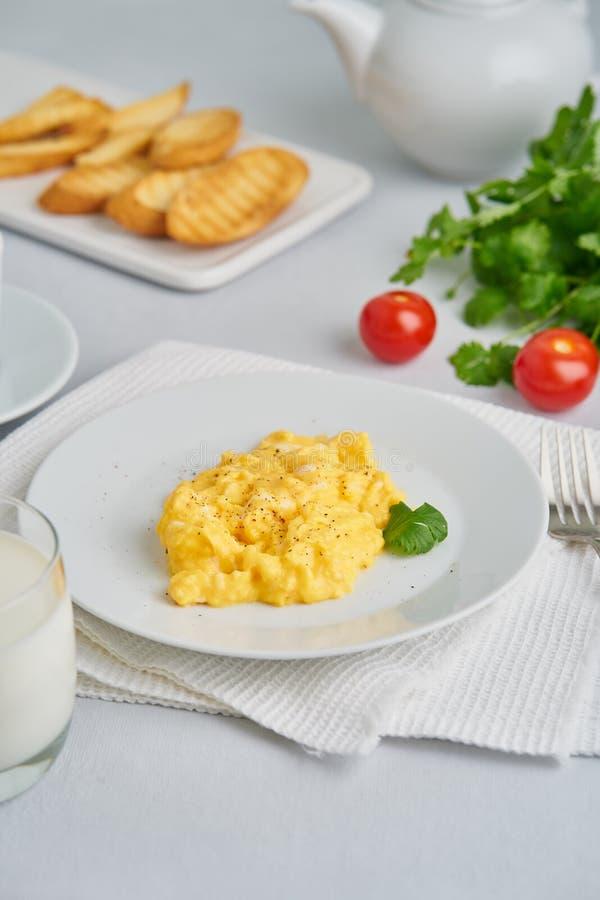 Взбитые яйца, омлет Завтрак со все-зажаренными яйцами, стекло молока, томатов на белой предпосылке r стоковое изображение
