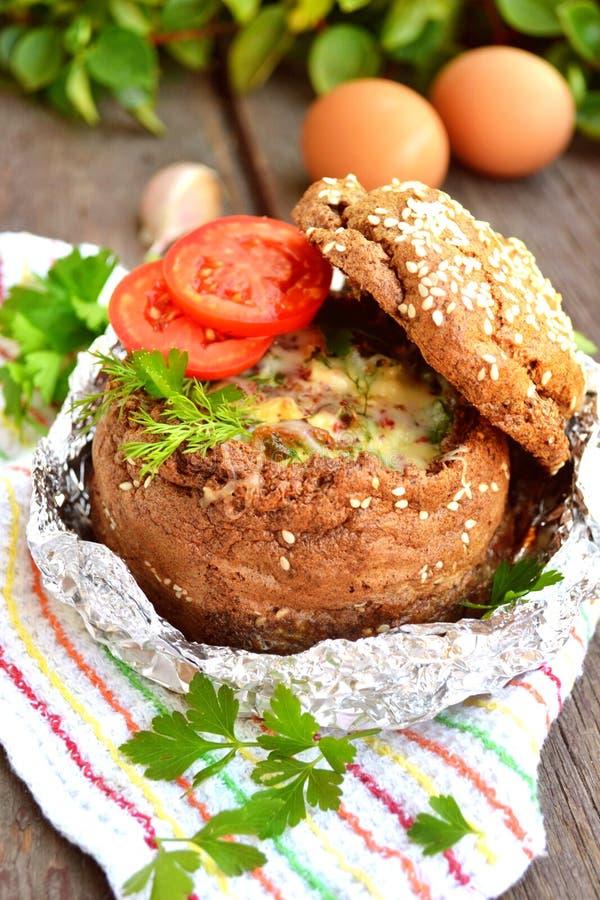 Взбитые яйца с беконом и овощами внутри шара хлеба стоковая фотография rf