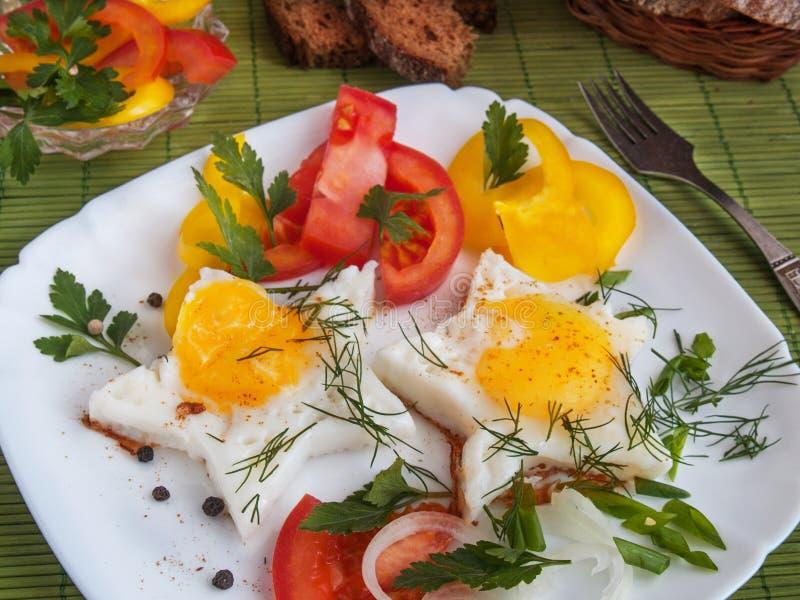 Взбитые яйца с овощами на белой плите стоковые фотографии rf