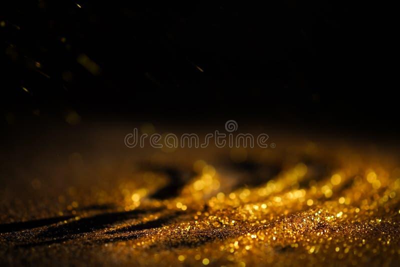 Взбрызните золотой песок на черной предпосылке стоковое изображение