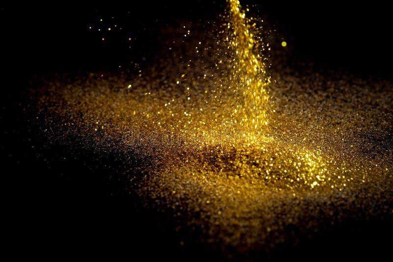 Взбрызните золотой песок на черной предпосылке стоковые фотографии rf