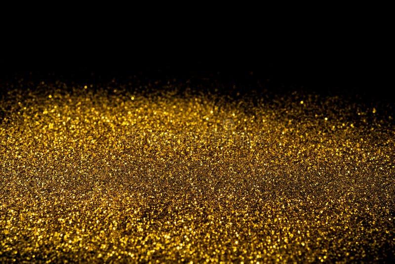 Взбрызните золотой песок на черной предпосылке стоковое изображение rf