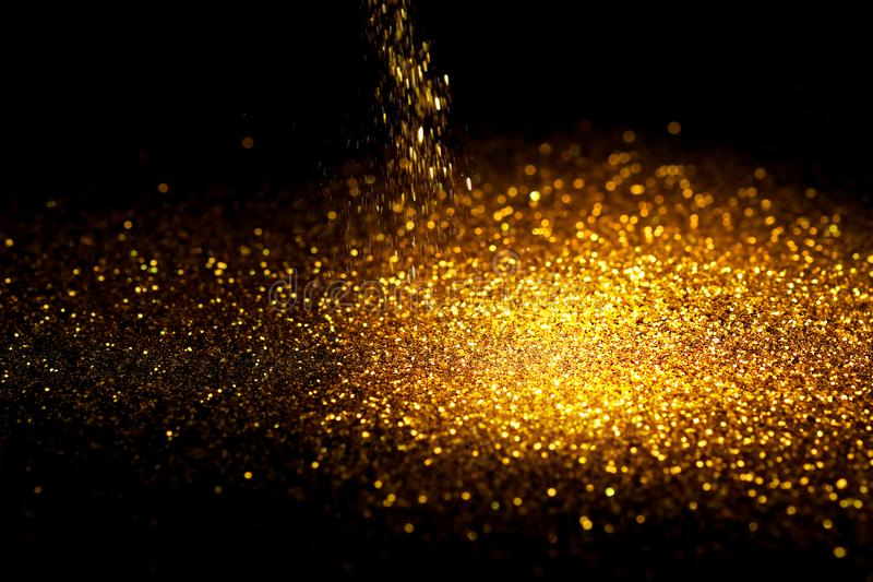 Взбрызните пыль яркого блеска золота на черной предпосылке стоковые изображения