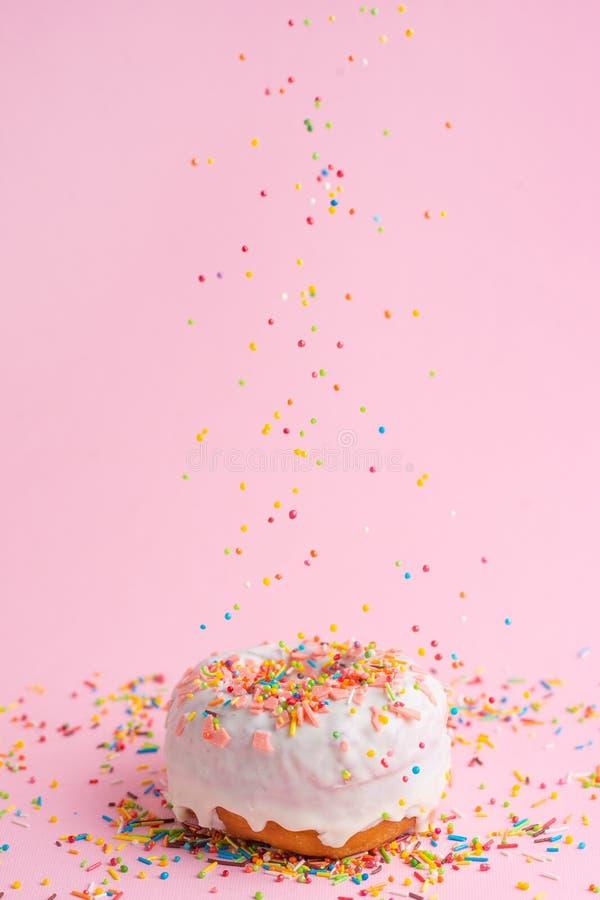 Взбрызните розовый донут на розовой предпосылке стоковые изображения