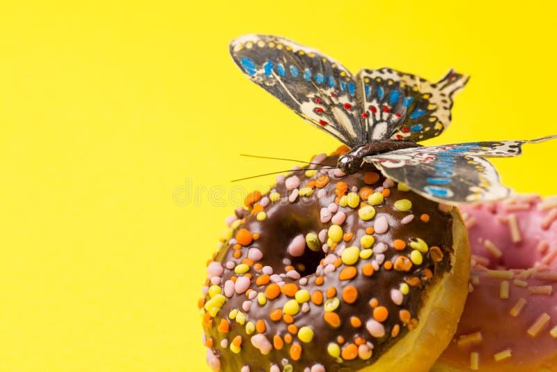 Взбрызнутый пинк и донут chokolate Замороженный взбрызнутый донут на желтой предпосылке стоковое фото