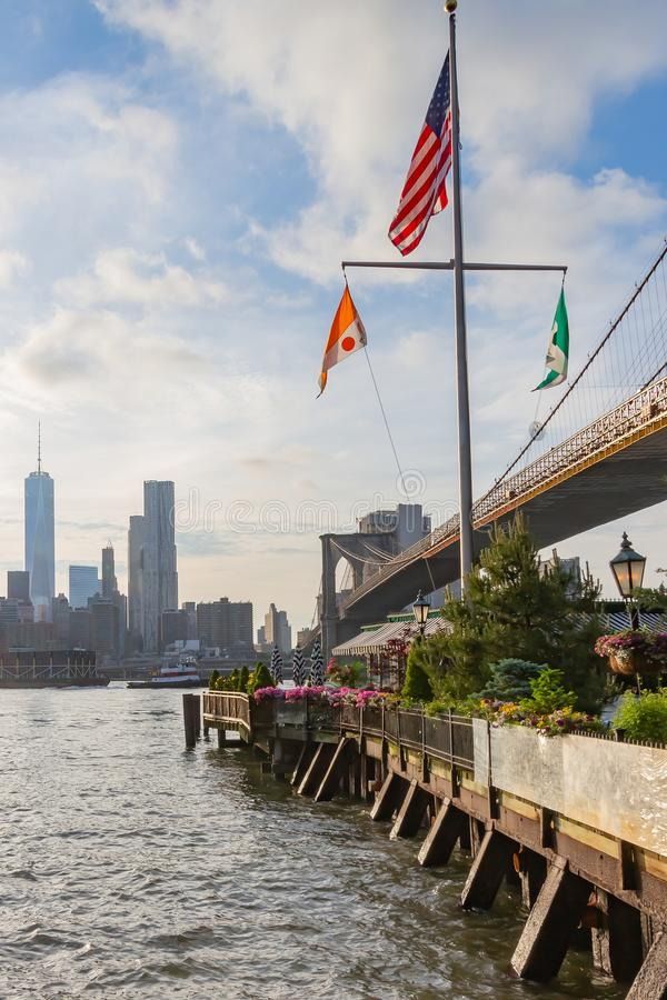 Взгляды Манхэттена вдоль Бруклинского моста и ресторанов вдоль Greenway парка Бруклинского моста, Нью-Йорка, Соединенных Штатов стоковые изображения rf