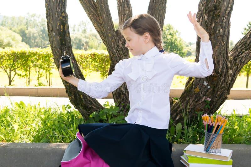 Взгляды удивленные на часах в снаружи лета, давно пора девушки для того чтобы пойти обучить стоковые фото