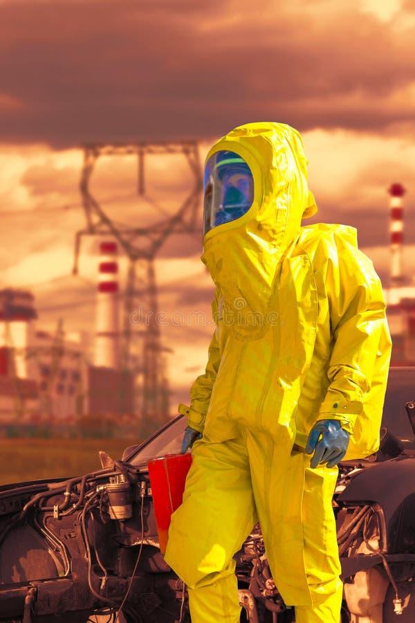 Взгляд атомной электростанции и пожарного в химическом защитном костюме hazmat стоковые изображения rf
