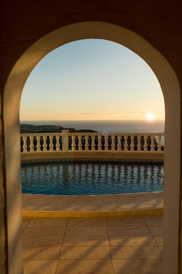 Взгляд бассейна через свод на заходе солнца стоковые изображения