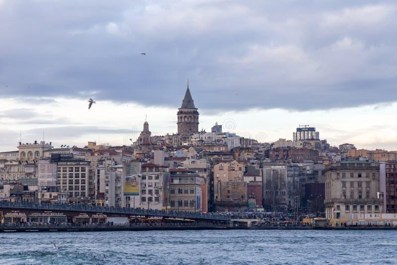 Взгляд башни Galata от взморья Eminonu Чайки летают морем Башня Galata одно из символического structur стоковое фото