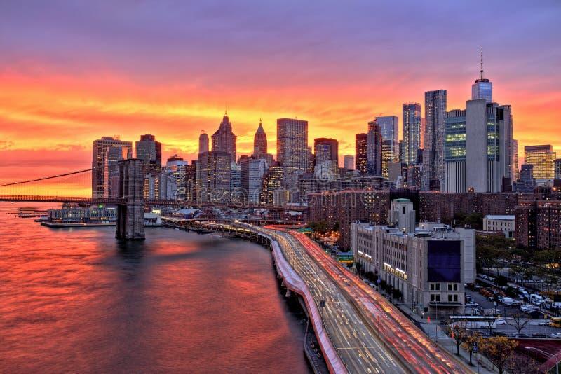 Взгляд более низкого Манхаттана с Бруклинским мостом на на изумительном заходе солнца, Нью-Йорком стоковое изображение rf