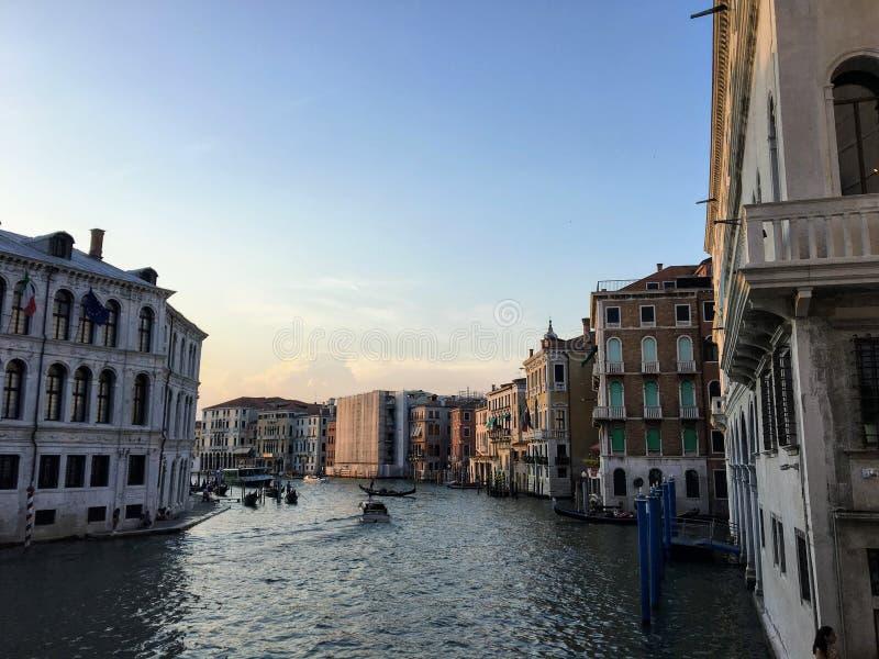 Взгляд большого канала в Венеции, Италии во время захода солнца Только немного маленьких лодок идя вниз с канала как наборы солнц стоковые фотографии rf