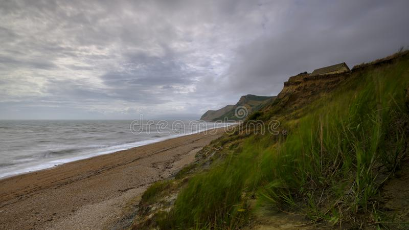 Взгляд вдоль побережья Дорсета от пляжа около Eype на ветреный день с долгой выдержкой приглаживая море и запачкать папоротники, стоковое изображение