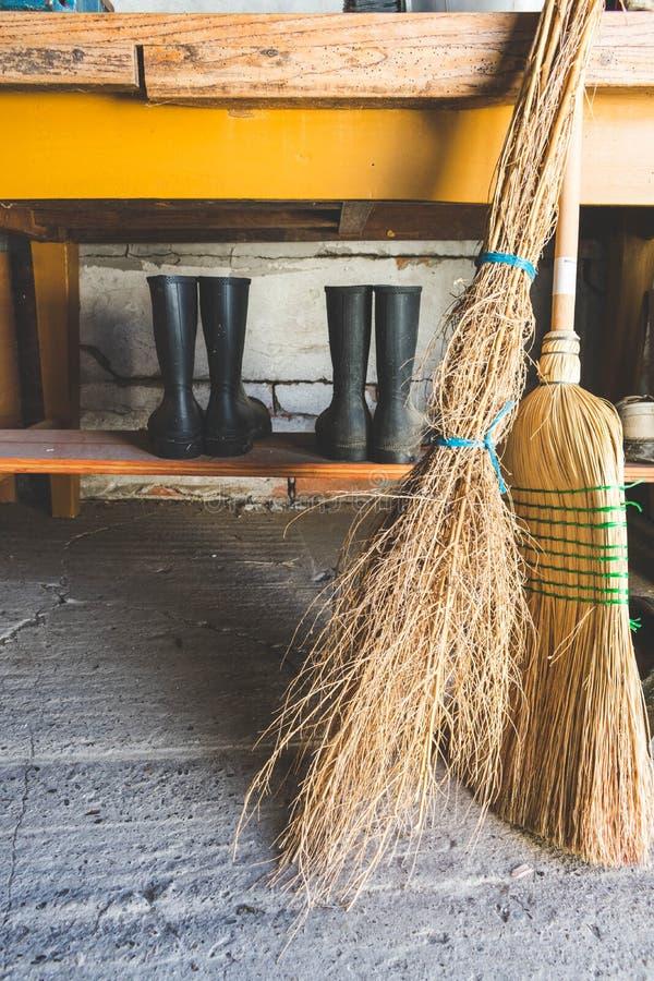 Взгляд веников и 2 пары резиновых ботинок под таблицей внутри в складском помещении стоковое фото rf