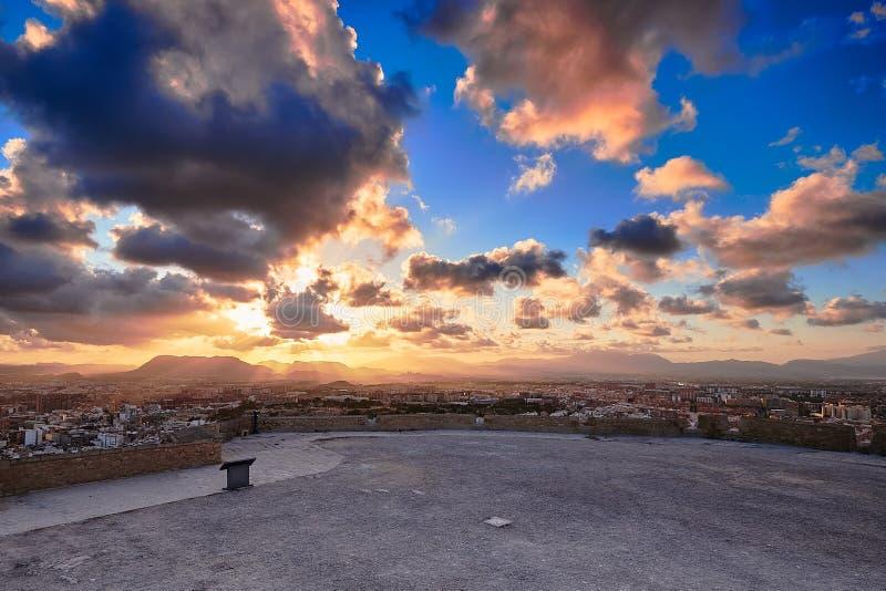 Взгляд вечера от смотровой площадки замка Санта-Барбара к городу и солнца в облаках за горами Аликанте стоковые фото