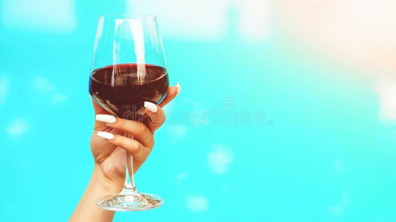 Взгляд вина и воды Женская рука держа стекло красного вина Каникулы перемещения Роскошный круиз r Hote роскошного курорта стоковое фото rf
