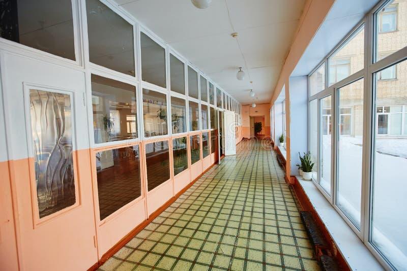 Взгляд внутри коридора входа, старых школы или жилого дома, дорожки мертвого конца длинной и узкой и стеклянного окна с стоковое фото