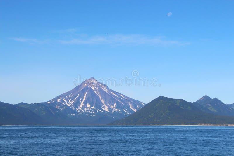 Взгляд вулкана Vilyuchinsky & x28; также вызвал Vilyuchik& x29; от воды Луна видима в небе стоковое изображение rf